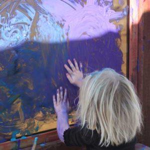 preschool child enjoying sensory painting and creativity