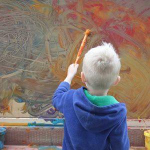 Preschool boy painting creatively