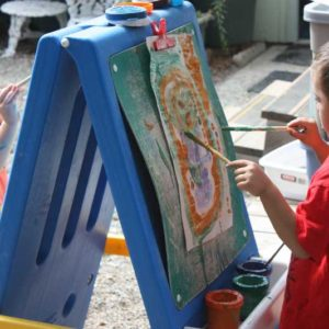 Preschool kids painting at an easel