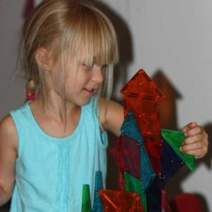 Happy preschool girl building higher