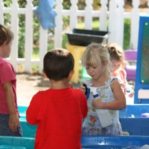 Preschool children engaged in play at the water tables