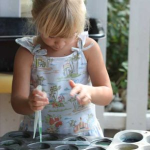 Preschool girl focused on paint color mixing