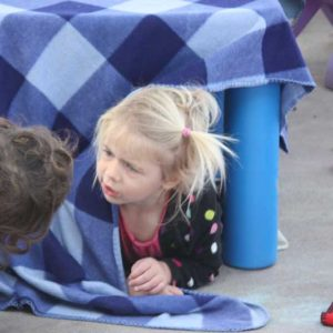 child building a fort under a blue table