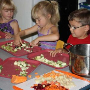 Group of preschoolers cutting veggies, learning about food and cooking