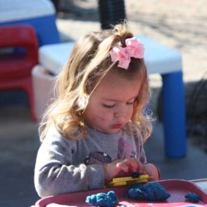 preschool girl building small muscles with play dough