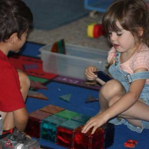 boy and girl building a friendship over magnetiles