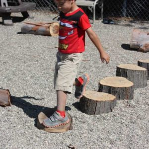 Preschool boy walking on tree stumps developing balance, eye foot coodination and motor planning