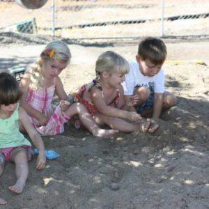 Preschool kids burying their feet in the sand