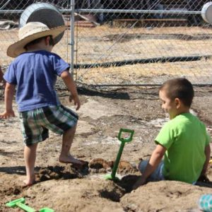 Preschool kids making rivers in the sand with water by digging and sqishing mud