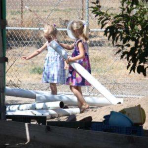 Preschool girls engaged in outdoor motor skills