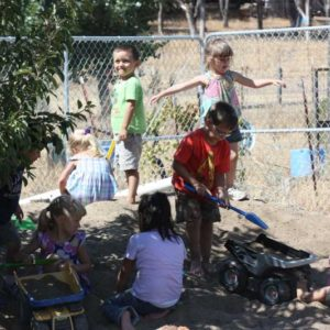 community of preschool children engaged in big body play in sand