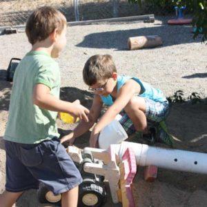 Preschool boys using tonka trucks to build with pipes