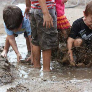 Delighted, preschool kids splashing in mud